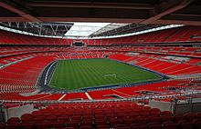 The interior of an empty stadium as viewed from its upper tier of seating. The seats are a vivid red and the pitch is a vivid green. The pale grey sky is visible through an opening in the ceiling above the pitch. Wembley Stadium is the biggest stadium in the UK.