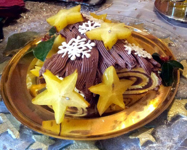 Tronchetto di Natale con ripieno di crema di marroni e copertura ganache al cioccolato, carambola e fiocchi di ghiaccia reale.
