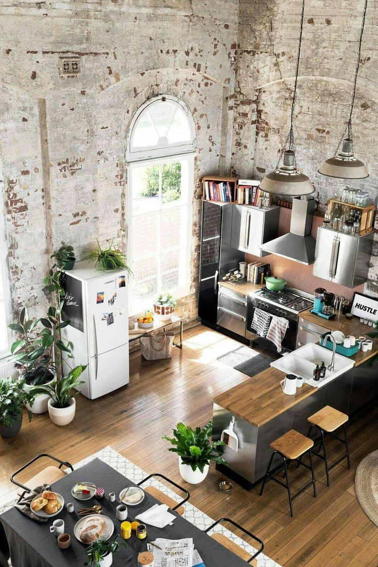 stainless steel kitchen, natural accents, high ceilings, whitewashed exposed brick