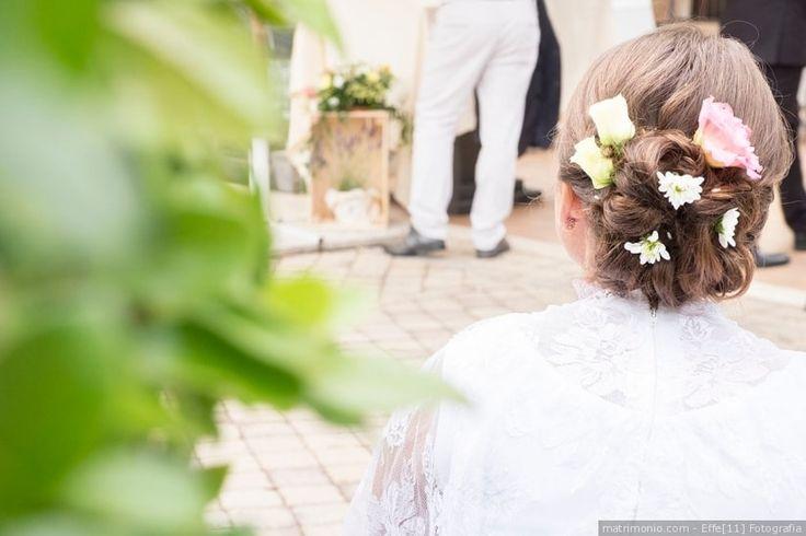 Acconciatura da sposa per capelli raccolti in uno chignon basso con fiori come accessorio sposa