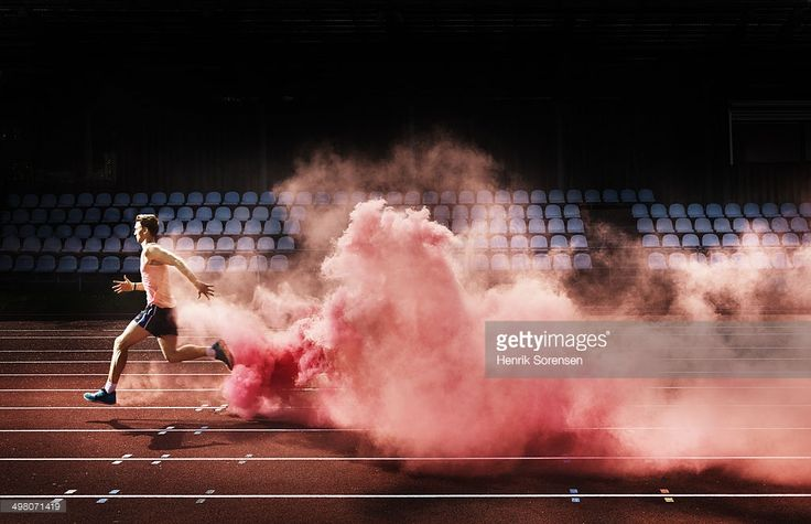 мужчины бег спортсмена в красный дым на стадион, оставляя за собой след из дыма