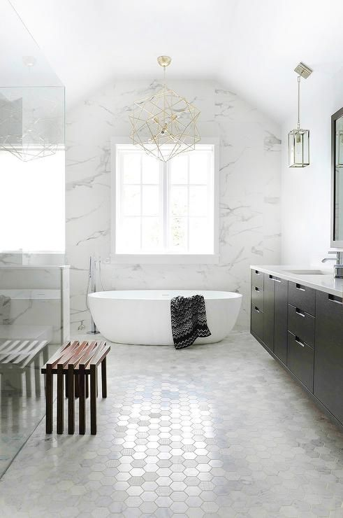 Black dual washstand topped with white quartz countertops stylishly contrasts white marble hex floor tiles, white marble walls, and a white oval freestanding tub.