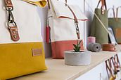 Backpacks and handbags on shelves for sale in a store by Luis Cerdeira - Stocksy United
