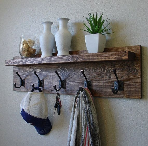 Handmade modern rustic coat rack with dark bronze hooks and floating shelf. Made from solid wood. It has been sanded down, then stained and sealed with