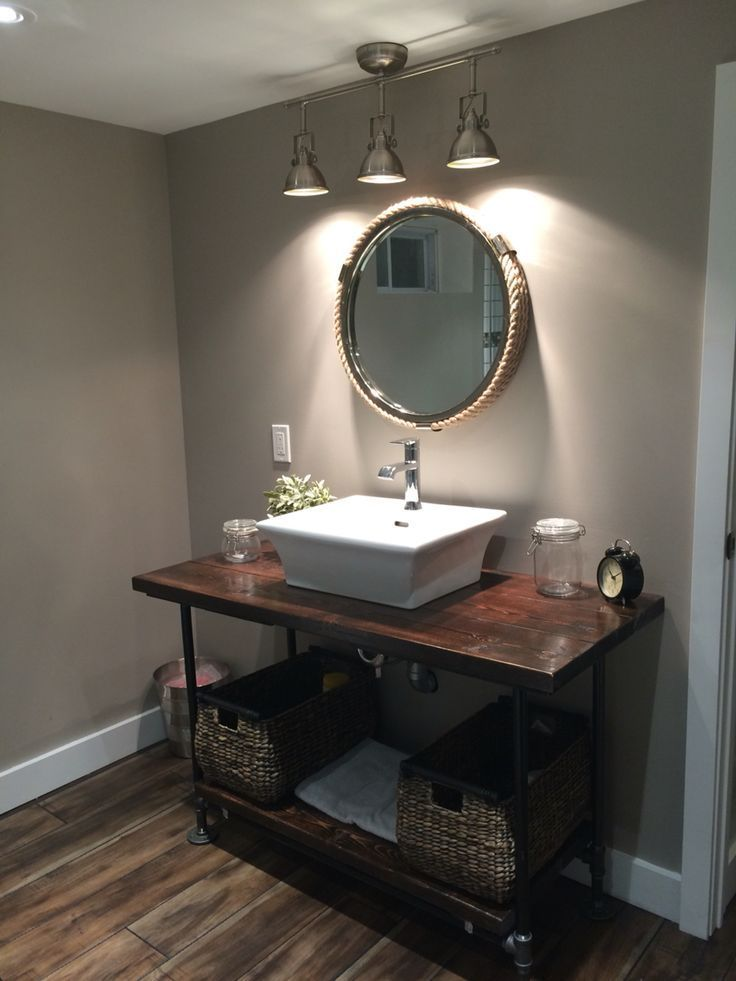 Small basement washroom remodel. Rustic DIY 2x4 stained wood countertop with pipe leg. Raised square Koehler sink with waterfall faucet. Storage baskets, circular rope mirror and industrial track lighting.