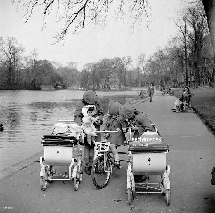 Sisters Margaret, Catherine and Vivian Moultrey playing in Raphael Park, Romford, with their dolls and toy prams.