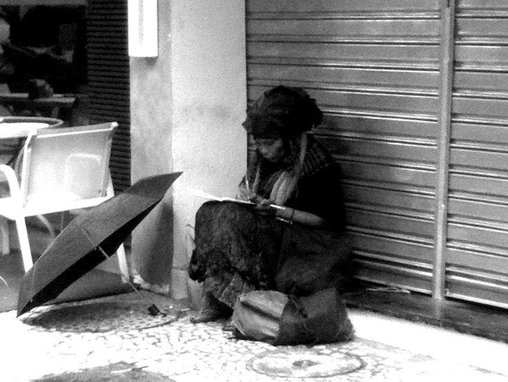 Uma mendiga escreve e fuma sob a marquise de uma loja. Eu escrevo e fumo em frente, confortavelmente sentada na cadeira de um Café. O que nos diferencia?