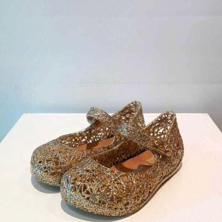 Le scarpe glitter con cinturino sono prodotte da Mini Melissa, che realizza queste calzature impiegando il 100% di plastica riciclata da una compagnia brasiliana impegnata socialmente ed eco-friendly.