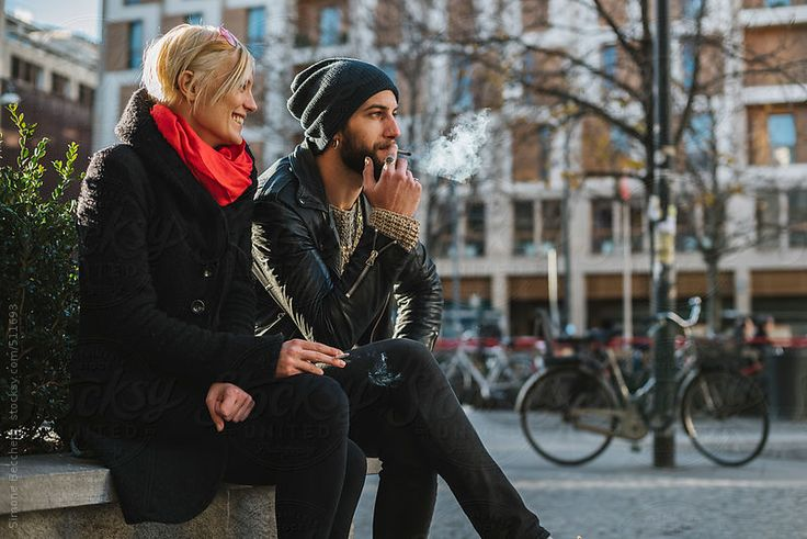 Young people smoking cigarette in the city.