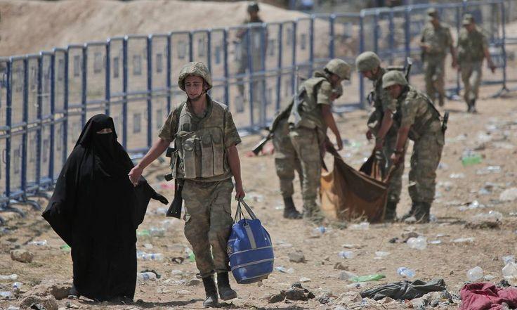Soldados do Exército turco ajudam uma síria e transportam uma pessoa doente em um cobertor Lefteris Pitarakis / AP