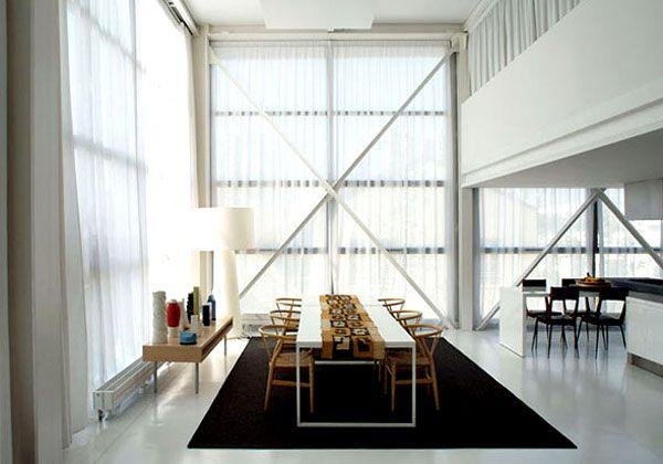 Un ampio tappeto scuro disegna lo spazio di questa essenziale e moderna sala da pranzo. Le linee rette del tavolo sono spezzate dagli schienali tondeggianti delle sedie in legno chiaro.VISITA LA CASA