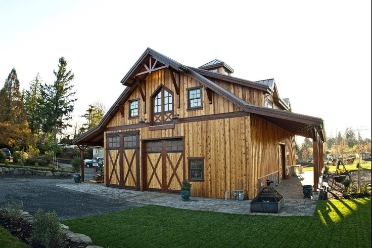 Custom timber framed barn in Sandy, OR with endless custom features such as copper wainscot on the exterior, log spiral case with a rod iron hand rail, and a covered deck and wet bar. Built by DC Building