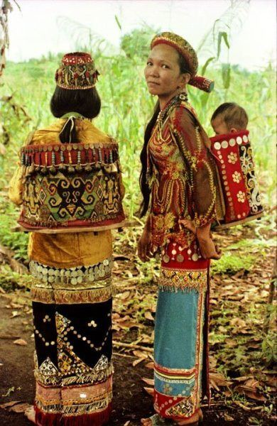 Indonesian women from Borneo with traditional costume. Notice the intricate patterns and embroidery.