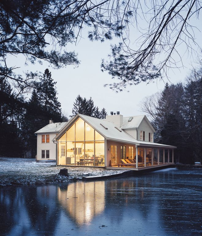 A self-taught designer embarks upon a solo mission to resuscitate a 19th-century homestead. The Floating Farmhouse's semitransparent addition has a roofline that matches the pitch of the original 1820s farmhouse. A porch, tucked under the side eaves, is cantilevered over a stream that runs through the property. Ikea loungers are illuminated from the interior by commercial gymnasium lights repurposed as pendant lamps. Photo by Mark Mahaney.
