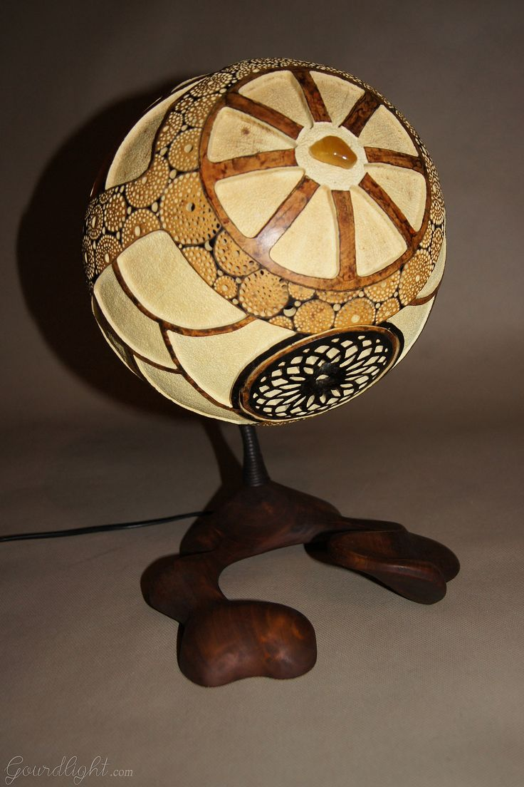 https://flic.kr/p/jDkLD9 | Table lamp IX | Head of the lamp is made of Senegalese calabash. White parts are carved layer of the fruit which change the color to red/orange when the lamp is switched on. On the bottom of the lamp there's perforated closing part locked by magnets. The lamp was painted with wood oil and alcohol ink. Black parts are burnt calabash surface. The center element is genuine Baltic amber- ranked as the world's finest;  resin from the ancient trees dating back ~40…