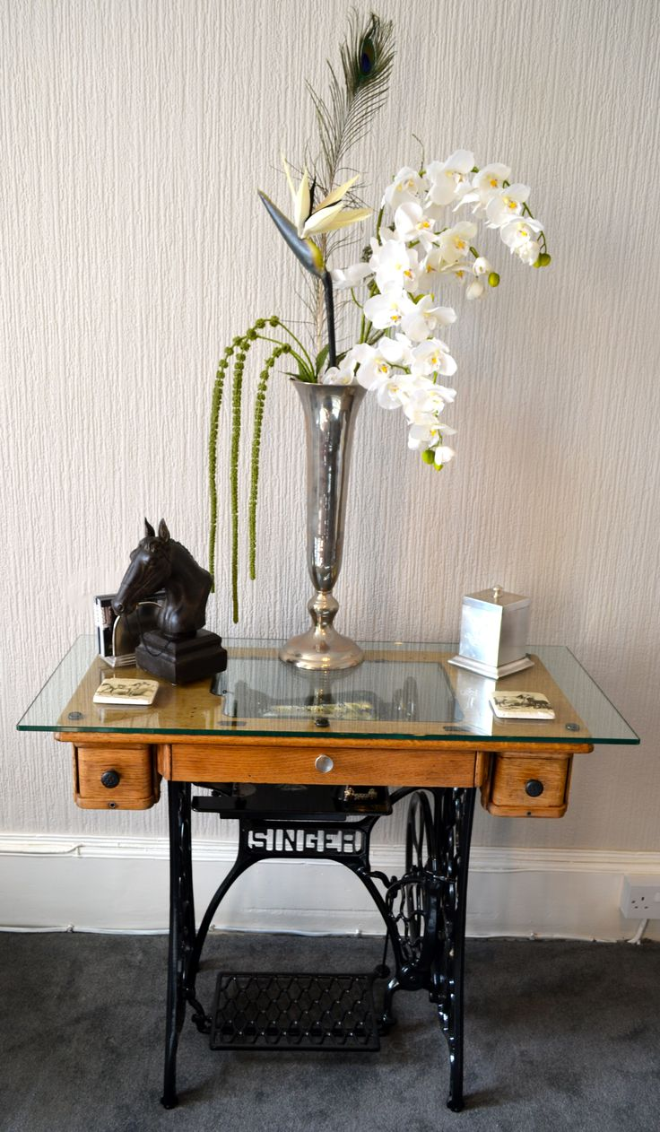 industrial past and present range side table. Made from cast iron antique singer sewing table. Keeping the historical essence of the Singer by mounting the original sewing machine on top of the cast iron base. Then by adding a clear 20mm acrylic insert in to the wood table top to view through the 10mm toughened glass top