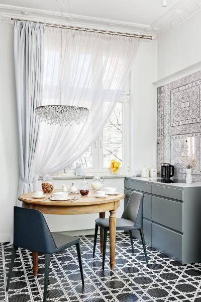 Klasyczną papierową tapetę Elitis zabezpiecza tafla z białego szkła. Pasuje do wzorzystej mozaiki firmy Bisazza na podłodze. Przy stoliku z pchlego targu stoją krzesła włoskiej marki Pedrali.