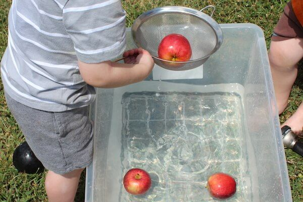 Fall preschool apple activity! Apple Bobbing activity using scoops for preschool apple theme fun.
