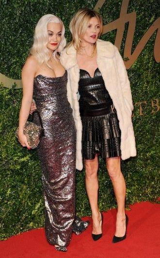 Rita Ora en Kate Moss poseren samen op de rode loper bij de British Fashion Awards. Rita Ora draagt een strapless jurk van Vivienne Westwood, Kate Moss en ontwerp van Marc Jacobs.