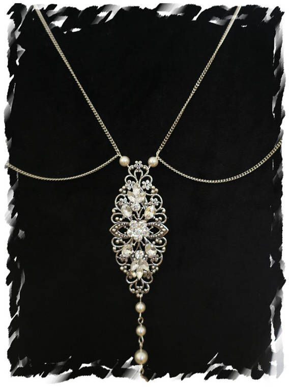 Vintage art deco inspired this statement bridal back silver chain necklace features white / ivory Swarovski pearls, different shape and size faceted crystals, leaf and flower embellishments and antique color rhodium chain  This design is perfect for art deco, Great Gatsby, Downton Abbey, Grecian, traditional, Old Hollywood style wedding and evening events  The necklace is about 26 long so there is no clasp but the size is enough for everyone to pass from head. (If you are going to have a…