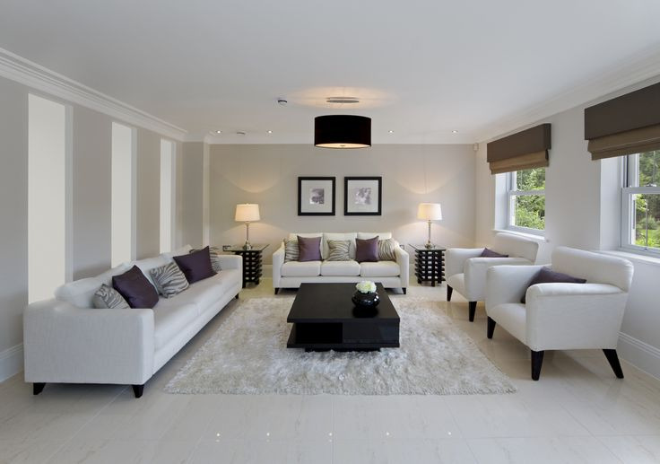 All white living room adds high contrast via central two-tier jet black coffee table standing on white rug over white marble flooring. White contemporary sofas and chairs stand on black wood frames, while singular cylindrical chandelier hangs above.
