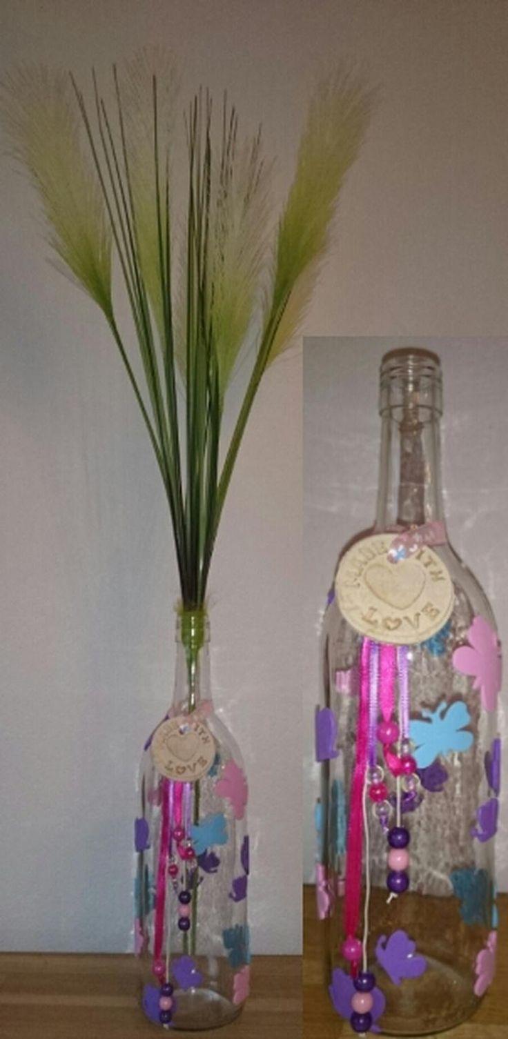 Foto: Lekker knutselen met Kinderen. Benodigdheden: glazen fles, stickers, lintjes, kraaltjes, embleem (in dit geval van zoutdeeg gemaakt, grote knoop kan ook) en je kunt er wat in zetten zijde of gewone bloemen. Net wat je leuk vindt. Maar leeg is de fles ook erg decoratief. Veel knutsel plezier!. Geplaatst door Broekkie op Welke.nl