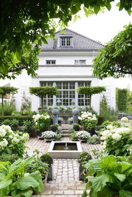 Symétrie parfaite des pots et plantes autour de cette fontaine pour un style classique. Www.monjardin-materrasse.com