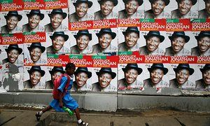 A schoolgirl walks past campaign posters in support of Nigeria's former president Goodluck Jonathan