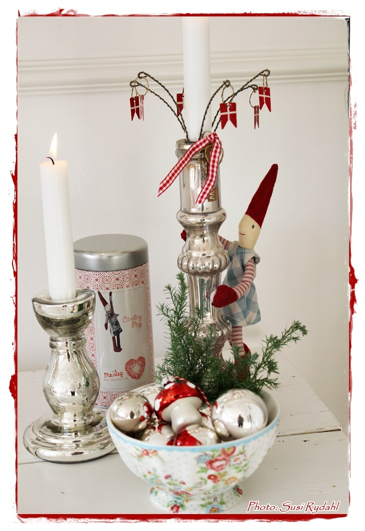Christmas decor - love the little flags around the candle and the little doll ::: Through the link I could not find this exact photo... but there's so many similar and sweet ones there.