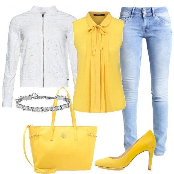 La camicetta gialla in seta con fiocco e colletto è abbinata a un paio di jeans slim fit chiari e la giacca leggera bianca traforata. Al polso il bracciale tennis. Gli accessori sono gialli: la borsa a mano con cerniera e le décolleté a punta in nabuk.