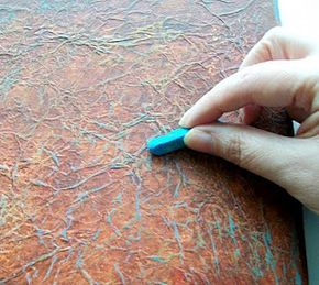 glue tissue paper over a canvas, let dry. paint, let dry, then rub pastel or chalk over the surface to highlight the texture.