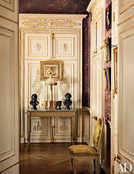 The main salon's doors, like those throughout the reimagined interiors, are embellished with distressed giltwork; above the 19th-century Italian console is an engraving by Jean-Hippolyte Flandrin.