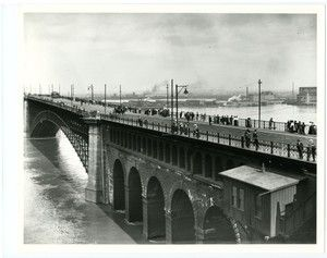 Horizontal, black and white photograph showing the Eads Bridge during high water in 1903. The bridge spans the center of the image. Pedestrians are crossing the bridge and peering over the edge at the Mississippi River. A carriage and streetcar can also be seen. Street lights and power lines line the bridge.