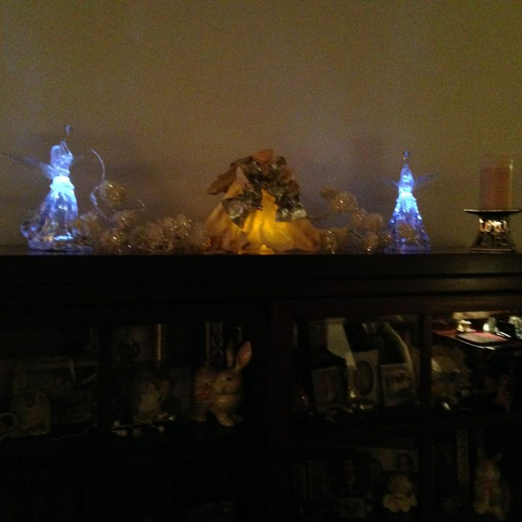 Angels lit up at night on top of barristers cabinet.