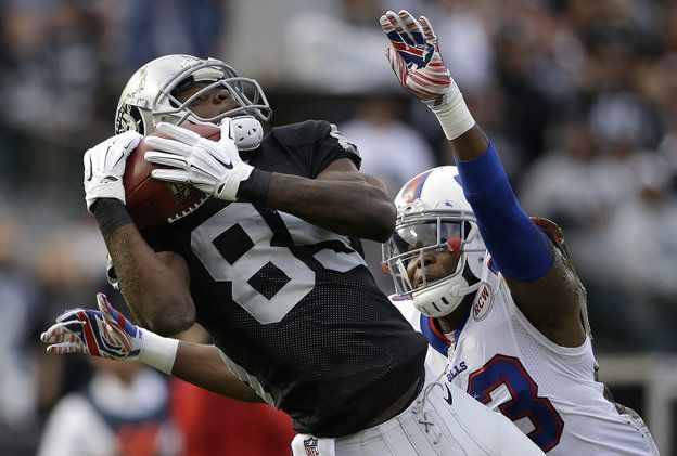 Oakland Raiders wide receiver Kenbrell Thompkins (85) catches a 50-yard pass in front of Buffalo Bills cornerback Aaron Williams during the first quarter of an NFL football game in Oakland, Calif., Sunday, Dec. 21, 2014. (AP Photo/Marcio Jose Sanchez)