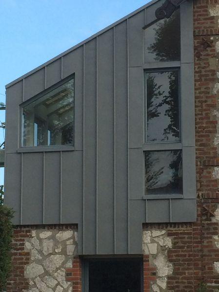 Bardage complet en zinc prépatiné quartz avec habillage des dormants de fenêtre.