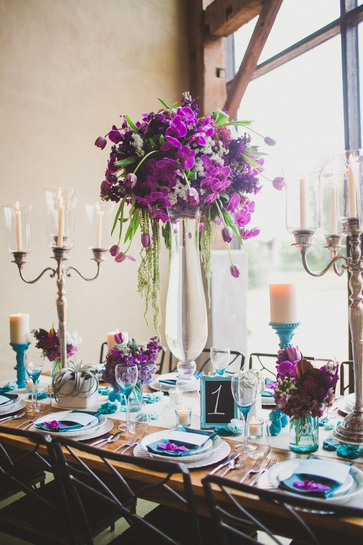 The head table will feature three crystal candelabras with two tall hourglass vases overflowing with purple hydrangeas and purple phalaenopsis orchids with single Picasso calla lilies submerged inside the vase.