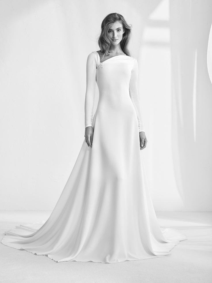 Raigal: Ein elegantes, raffiniertes Brautkleid. Bezaubernder asymmetrischer Ausschnitt mit Drapierung und Wasserfall-Rundausschnitt am Rücken. Pronovias