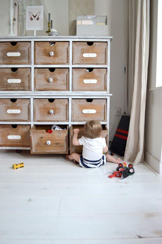 Opbergen in houten vakkenkast met opschriften.