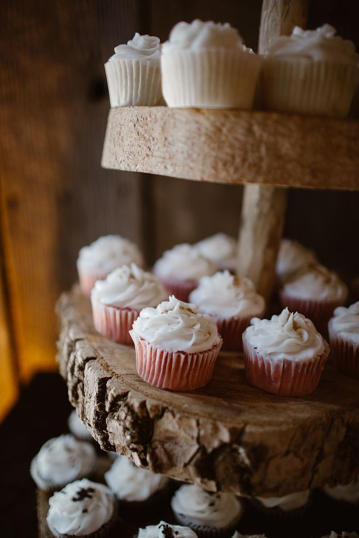 Rustic wooden cupcake stand with white cupcakes.