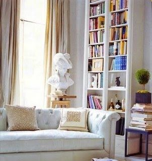 Home library. White, built-in bookcases to the ceiling with a little bar incorporated into the bookshelf.