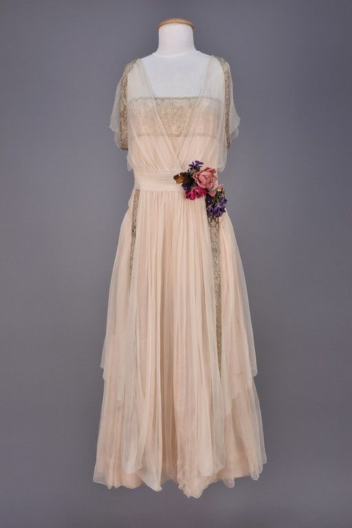CHIFFON and METALLIC LACE EVENING DRESS, c. 1918. White silk having sheer sleeveless V-neck bodice with silver lace trim and beaded back tassel over short sleeve bodice with wide silver lace band, vertical lace bands edge front and back looped panels over full skirt, pale pink silk lining, cloth flowers at waist. Unlabeled.
