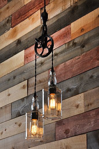 A cool pulley pendant lamp with two whiskey bottles and vintage filament lightbulbs. Great rustic decor.