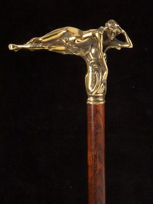 a brass tau shaped reclining Lady French date circa: 1900 a fine tau shaped bronze handle of a reclining nude, in good detail, mounted directly onto a rich pattern rosewood dark brown shaft ~ length of handle 7cm / 2.7in, width of handle 10.5cm / 4.1in, overall length 94cm / 36.7in.