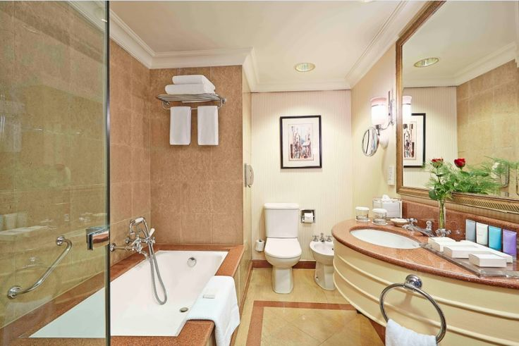 A marble bathroom with luxurious amenities, bath tub and walk in shower - at ConradCairo.