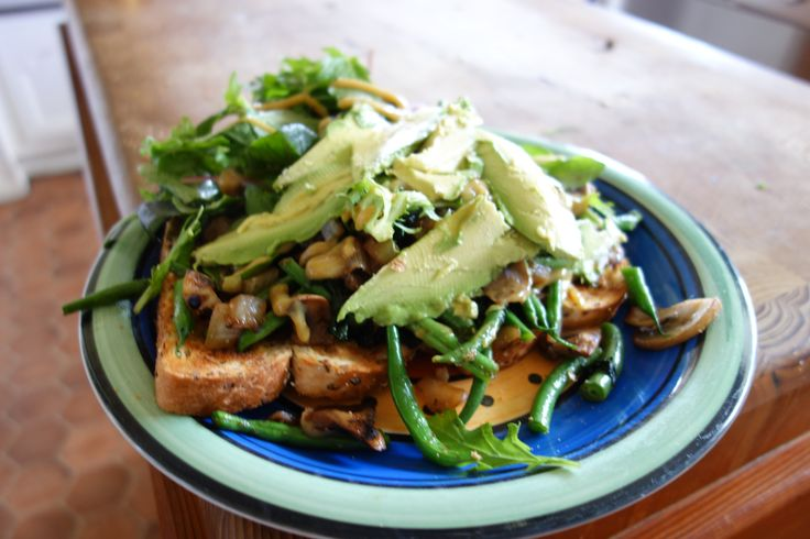 Fried onion, mushrooms and beans, on wholegrain toast. Topped with avocado rocket and mustard.