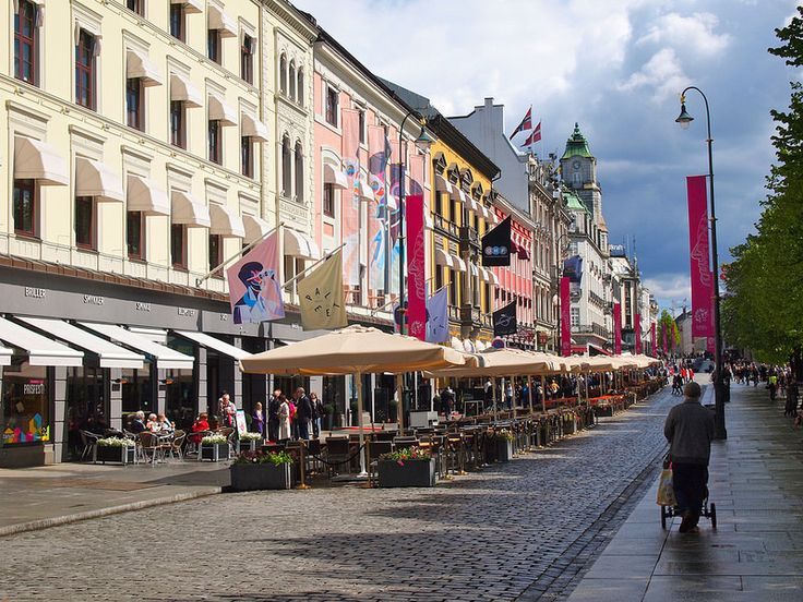 Karl Johans Gate in Oslo, Norway. The main street in the center of Oslo that leads from the train station to the Royal Palace. It's colorful and partially tree-lined, and would be a great place to sit down and sip on a cup of coffee.