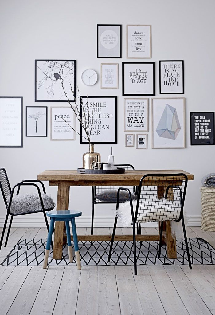 Nordic-style dining room: rustic table, modern stool and chairs, gallery of framed art and favorite quotes.