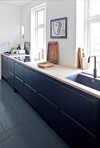 Køkkenet, armaturer og håndvaske er fra Box One. De gamle skærebrætter og fade har Rikke købt på sine rejser. Billedet ved vinduerne er af Knud Odde. På bakken fra Louise Roe står krukker fra Royal Copenhagen, en morter fra Ikea og en PH-lampe, som giver en hyggelig belysning.