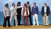 Seven men in suits standing near the ocean posing for a photo.  Fat Freddy's Drop